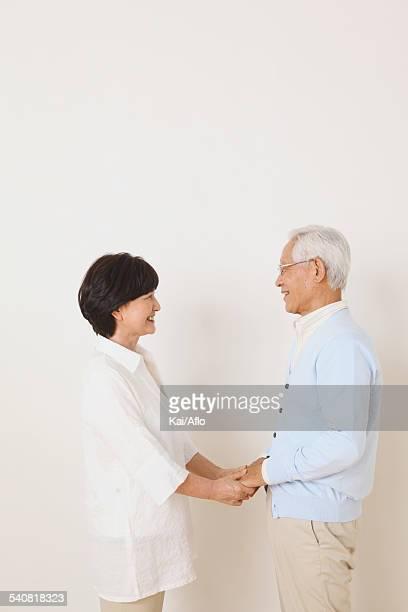 Senior adult Japanese couple against white wall