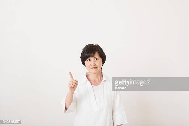 Senior adult Japanese woman against white wall