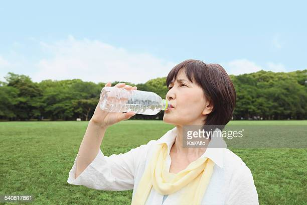 Senior adult Japanese woman drinking water in a park