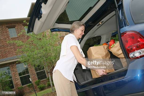 Senior Adult Lifting Groceries from Car in front of house