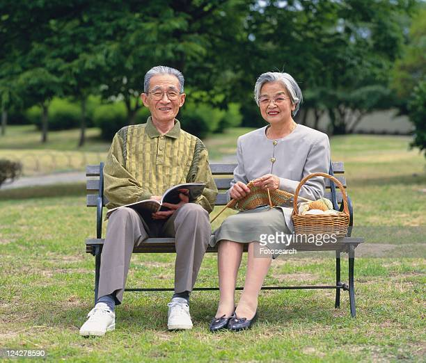 Senior adult man and woman sitting together on a bench, Front View