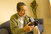 A Senior Adult Man Caring His Camera, Side View, High Angle View
