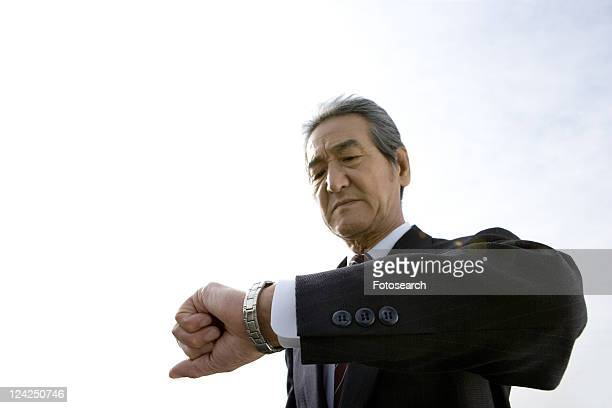 A Senior Adult Man Checking the Time with His Watch, Low Angle View