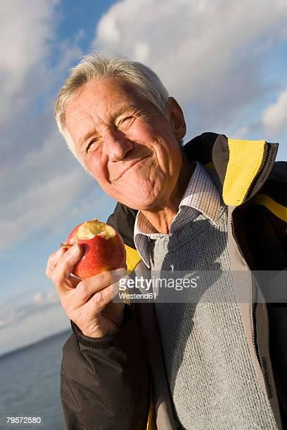Senior adult man eating apple