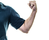 A physically fit senior adult man is is flexing his arm and forearm muscles with an upraised, clenched fist. Cropped image. Concepts of senior adult fitness, senior adult power, strength, determinatio