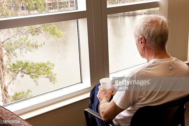 Senior adult man hospital patient waiting by window. Looking. Room.