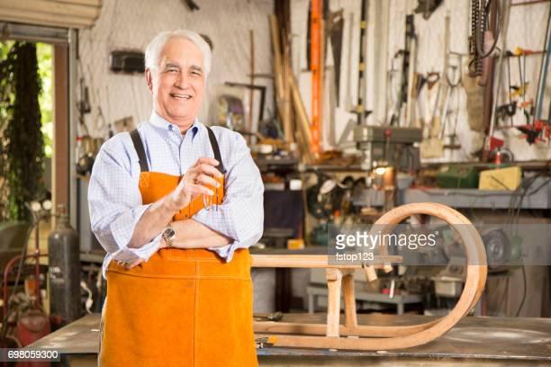 Senior adult man restores antique furniture.