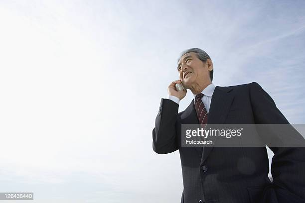 A Senior Adult Man Smiling and Talking on a Mobile Phone Under the Sky, Low Angle View, Copy Space