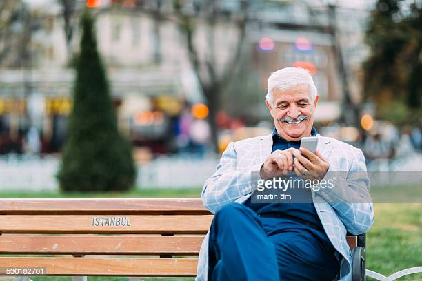 Senior adult man texting while resting outside
