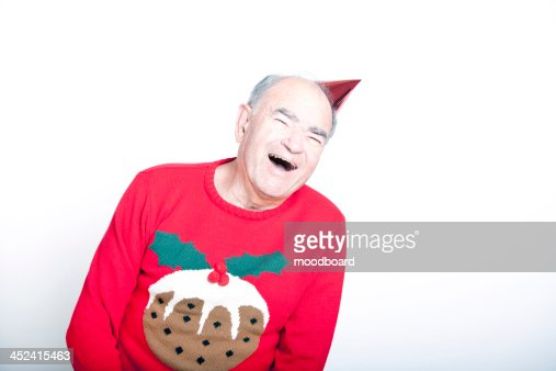 Senior adult man wearing a Christmas jumper and a red party hat : Stock Photo