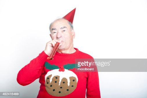 Senior adult man wearing Christmas jumper blowing party blower : Stock Photo