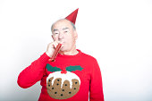 Senior adult man wearing Christmas jumper blowing party blower
