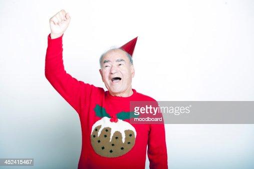 Senior adult man wearing Christmas jumper raising his arm in the air : Stock-Foto