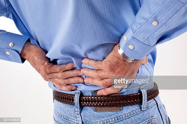 Senior adult man with back pain, rubbing his lower backache.