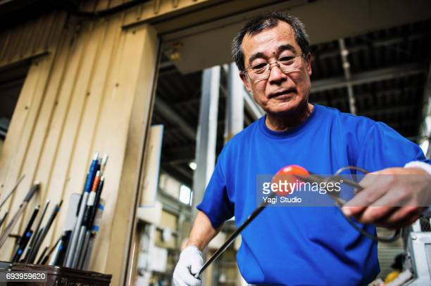 Senior adult man working in glass factory
