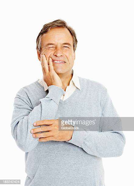 Senior adult suffering from a toothache against white