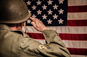 Senior adult man in military combat uniform saluting the American flag.  Rear view.