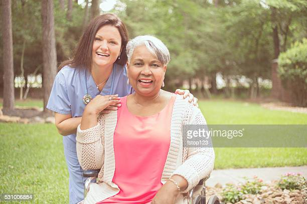 Senior adult with home healthcare nurse, caregiver outdoors.  Home, wheelchair.
