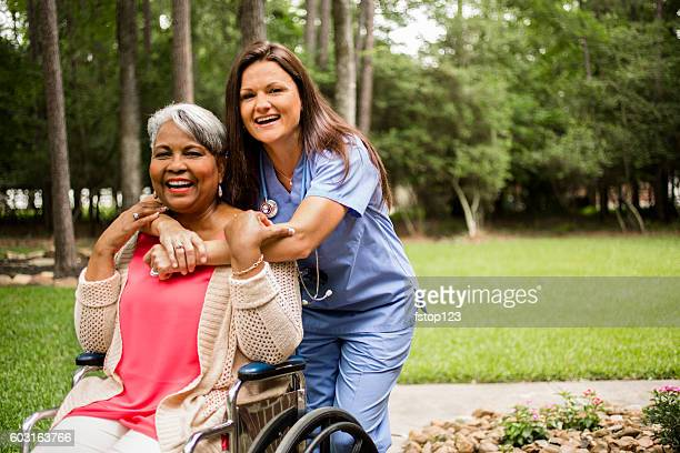 Senior adult with home healthcare nurse, caregiver outdoors.
