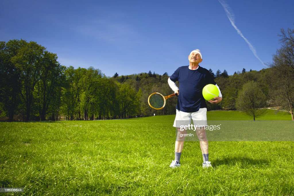 Senior adult with tennis racket in the park : Stock Photo