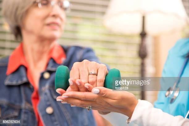 Senior adult woman and home healthcare nurse, physical therapist.