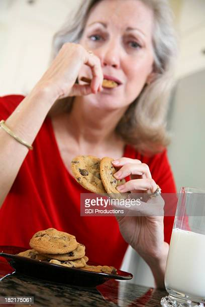 Senior Adult Woman Enjoying Her Cookies and Milk