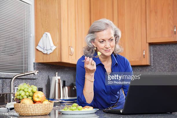 Senior adult woman having breakfast in kitchen while on laptop