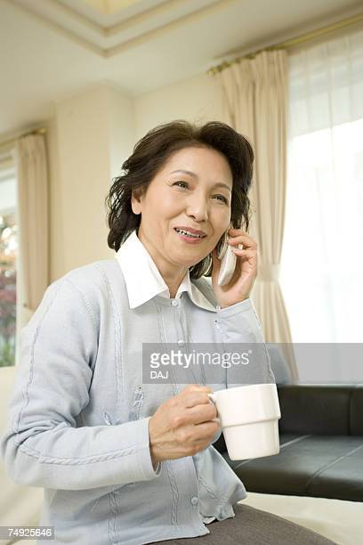 A Senior Adult Woman Holding a Cup and Talking on a Mobile Phone, Side View, Front View, Differential Focus