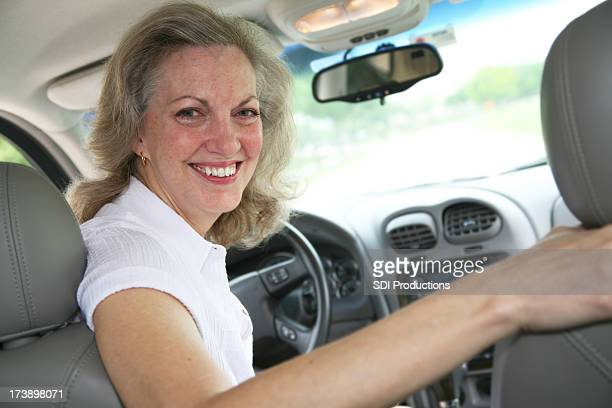 Senior Adult Woman Looking Back From the Car Driver's Seat