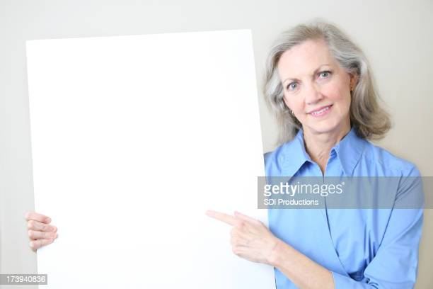 Senior Adult Woman Pointing to a Blank White Sign