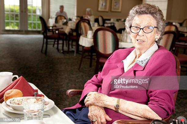 Senior Adult Woman Sitting at Dinner Table in Dining Hall