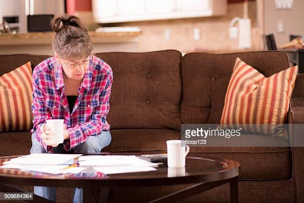 Senior adulte femme a des difficultés pour payer les factures en souffrance. Chez vous.