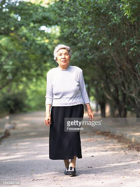 Senior adult woman taking a walk, Front View