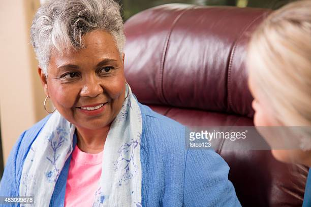 Senior adult woman talking with home healthcare nurse.