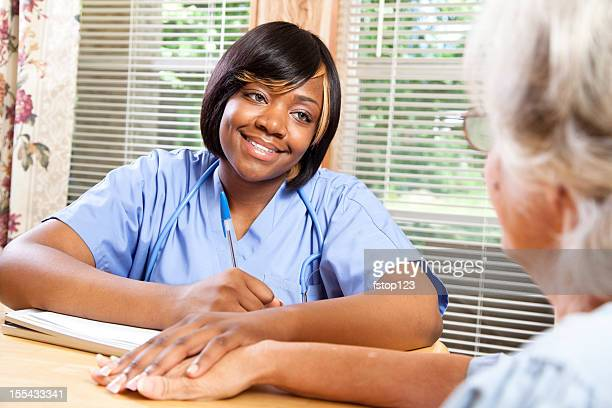 Senior adult woman visiting with home healthcare nurse. Assisted living.