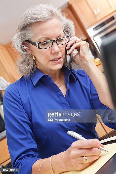 Senior adult woman working on phone and laptop in kitchen