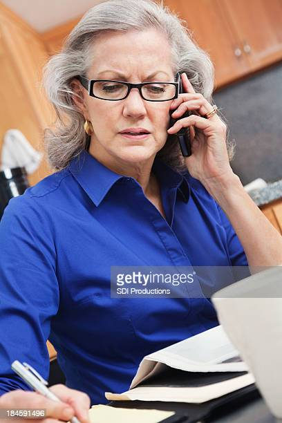 Senior adult woman writing while on phone in her kitchen