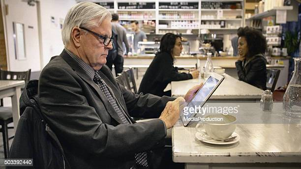Senior adult working on a tablet in a cafe