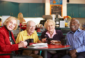 A group of four seniors sits at a round red table for morning tea from black mugs.  They are all smiling and adorned in colorful clothing.  The kitchen in the background is cream colored with teal cab