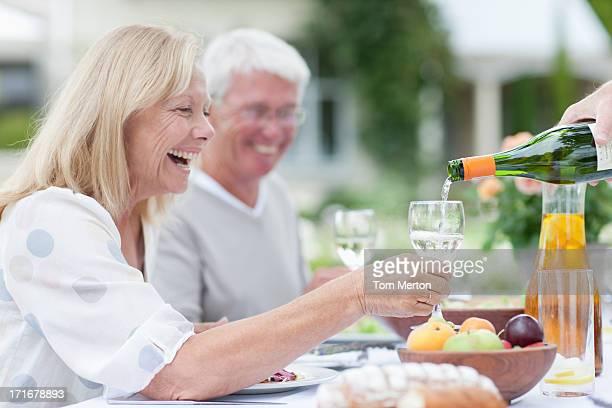 Senior adults enjoying wine at patio table