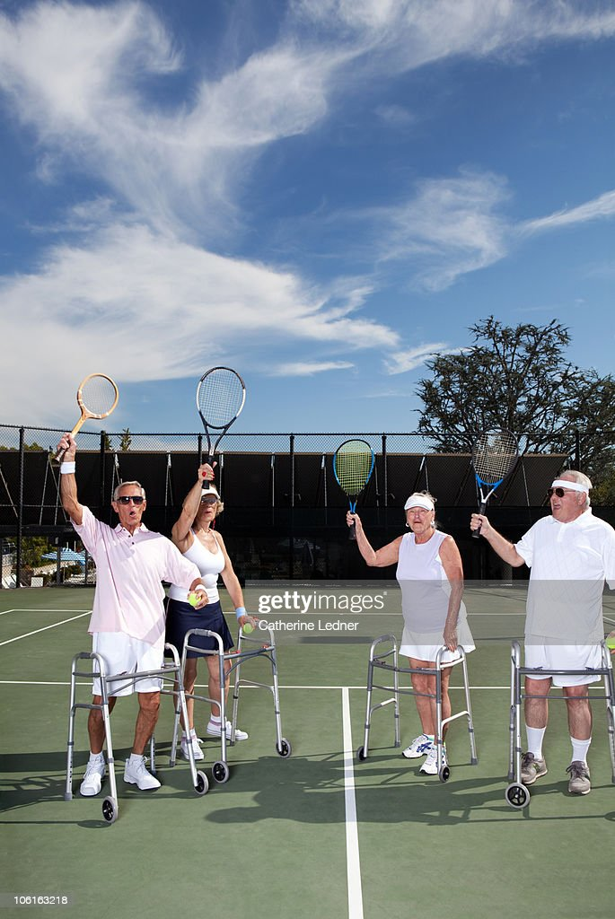 Senior adults playing tennis with rackets raised : Stock Photo