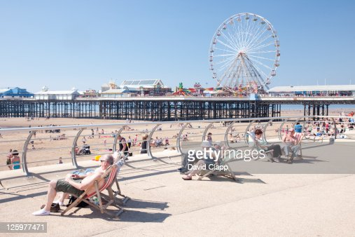 Senior adults relaxing in sun on Blackpool Beach Promenade, Blackpool, Lancashire, England, UK