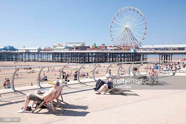 Senior adults relaxing in sun on Blackpool Beach Promenade, Blackpool, Lancashire, England, UK