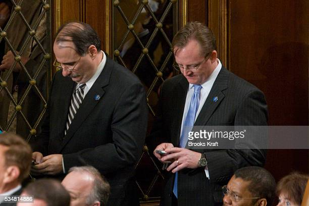 Senior Advisor David Axelrod and Press Secretary Robert Gibbs use their blackberry PDAs as US President Barack Obama delivers his first State of the...