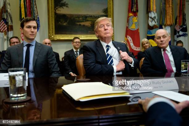 Senior Advisor Jared Kushner and Secretary of Homeland Security John Kelly listen while US President Donald Trump puts his papers away at the...