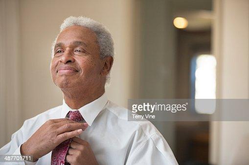 Senior African American businessman adjusting his tie