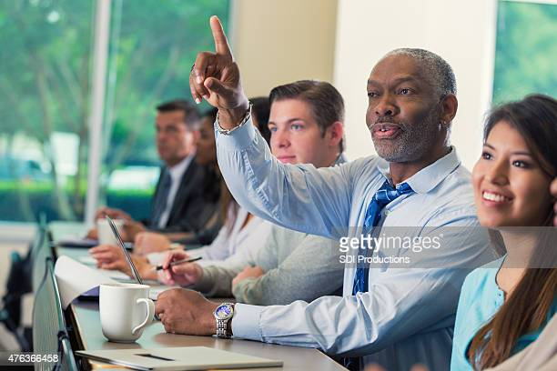 Senior African American businessman asking question during business seminar conference