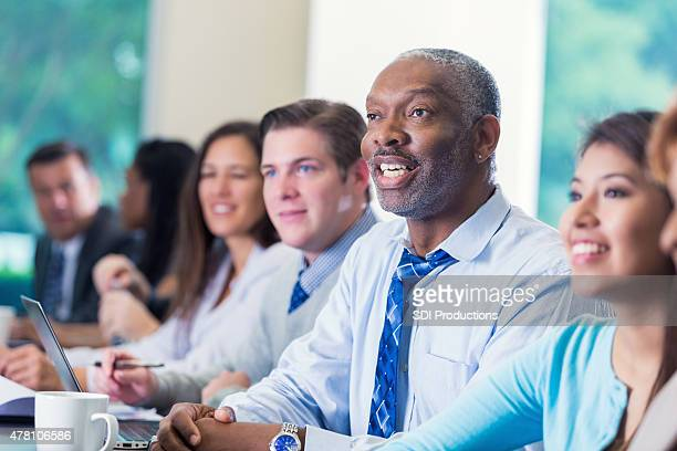 Senior African American businessman asking question in business conference