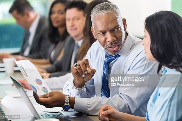 Senior African American businessman discussing financial charts during business conference