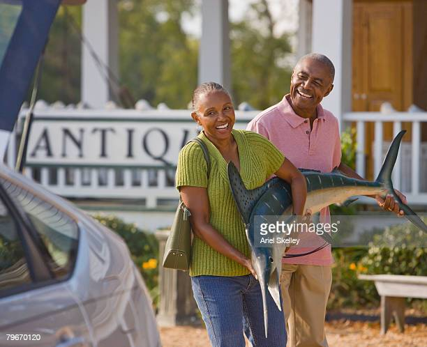 Senior African American couple carrying swordfish